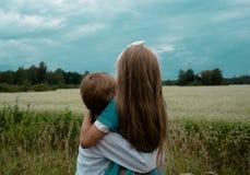 Abarcamiento que se sienta de la muchacha y del muchacho en fondo del campo del verano Imagen de archivo libre de regalías