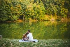Abarcamiento que se sienta de los pares cariñosos hermosos por el río Imagenes de archivo