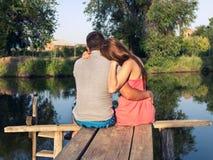 Abarcamiento que se sienta de los pares jovenes en el puente por el río Imagen de archivo libre de regalías