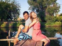 Abarcamiento que se sienta de los pares jovenes en el puente por el río Fotografía de archivo libre de regalías