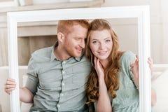 Abarcamiento que se sienta de los pares jovenes en el sofá y mirada a través del marco blanco Imagen de archivo libre de regalías