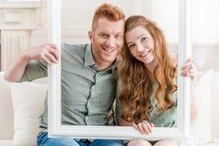Abarcamiento que se sienta de los pares jovenes en el sofá y mirada a través del marco blanco Foto de archivo