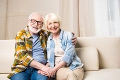 Abarcamiento que se sienta de los pares mayores en el sofá y sonrisa en la cámara Imágenes de archivo libres de regalías