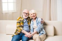 Abarcamiento que se sienta de los pares mayores en el sofá y sonrisa en la cámara Foto de archivo libre de regalías