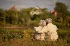 Abarcamiento que se sienta de los pares mayores felices en parque del otoño Fotografía de archivo libre de regalías