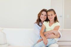 Abarcamiento sonriente de la madre y de la hija Imagenes de archivo