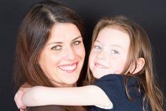 Abarcamiento sonriente de la madre y de la hija Imagen de archivo libre de regalías