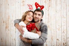 Abarcamiento sonriente de los pares jovenes sosteniendo el regalo de la Navidad sobre fondo de madera Imagen de archivo