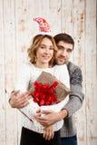 Abarcamiento sonriente de los pares jovenes sosteniendo el regalo de la Navidad sobre fondo de madera Fotos de archivo