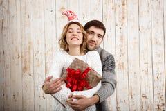 Abarcamiento sonriente de los pares jovenes sosteniendo el regalo de la Navidad sobre fondo de madera Imágenes de archivo libres de regalías