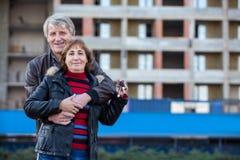 Abarcamiento sonriente feliz de los pares al aire libre con llave de la casa a disposición, copyspace Imagen de archivo