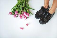 Abarcas de cuero negras de moda finas en las piernas de las mujeres con las flores Imagenes de archivo
