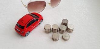 Abarth Eds Fiat 500 Spielzeug auf weißer Tabelle nahe Sonnenbrille und Stapel von israelischen Schekelmünzen lizenzfreies stockbild