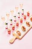 Abasteciendo, banquete, concepto de la comida del partido sobre fondo del rosa en colores pastel Imagen de archivo