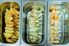Abasteciendo cocinando los pinchos del pollo y de los pescados, torta, bocado, empanada Fotografía de archivo