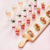 Abasteciendo, concepto de la comida del banquete sobre fondo del rosa en colores pastel Fotografía de archivo libre de regalías