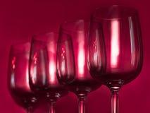 Abasteciendo, concepto del partido: copas de vino en un fondo de rubíes Foco selectivo Imagen de archivo libre de regalías