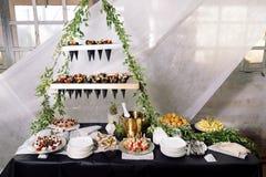 Abasteciendo, una tabla de la boda con el champán, frutas, bocados Imagen de archivo