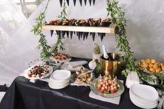 Abasteciendo, una tabla de la boda con el champán, frutas, bocados Foto de archivo