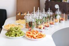 Abastecimiento del banquete de boda Un montón de diversas clases mezcladas de fruta cortada, verduras, queso, ensaladas en tazas  Foto de archivo libre de regalías