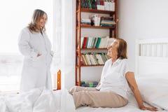 Abastecimiento del cuidado para los ancianos Doctor que visita al paciente mayor en casa Imagen de archivo libre de regalías