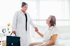 Abastecimiento del cuidado para los ancianos Doctor que visita al paciente mayor en casa Imagen de archivo