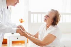 Abastecimiento del cuidado para los ancianos Doctor que visita al paciente mayor en casa Fotos de archivo libres de regalías