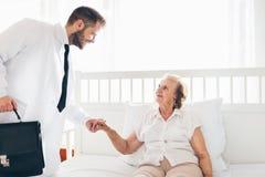 Abastecimiento del cuidado para los ancianos Doctor que visita al paciente mayor en casa Imágenes de archivo libres de regalías