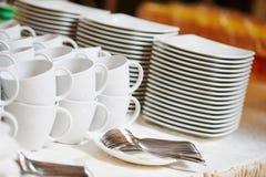 Abastecimiento del desayuno Placas y tazas blancas limpias vacías Imagen de archivo libre de regalías