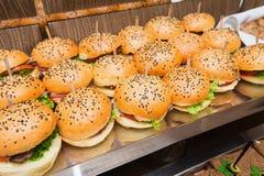 Abastecimiento en el evento - tabla servida con bocado de las hamburguesas Fotografía de archivo libre de regalías