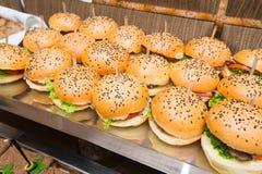 Abastecimiento - tabla servida con bocado de las hamburguesas Imágenes de archivo libres de regalías