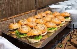Abastecimiento - tabla servida con bocado de las hamburguesas Fotografía de archivo libre de regalías