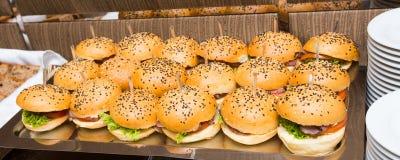Abastecimiento - tabla servida con bocado de las hamburguesas Imagen de archivo