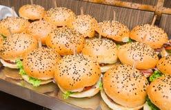 Abastecimiento - tabla servida con bocado de las hamburguesas Foto de archivo