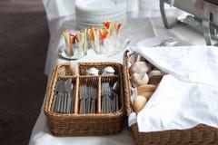 abastecimiento Una cesta del pan con los cubiertos y los bocados para los cócteles fotografía de archivo libre de regalías