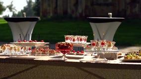 Abastecimiento, una tabla hermosa con bocados y platos Canape en tazas metrajes