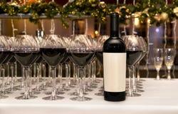 abastecimiento Vidrios y botella con el vino rojo Foto de archivo
