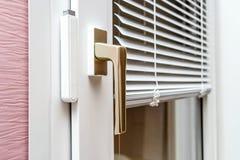 Abat-jour d'aluminium sur la fenêtre de PVC Images stock