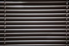 Abat-jour dans une maison attrapant la lumière du soleil, dos de fenêtre de volet en métal Images stock