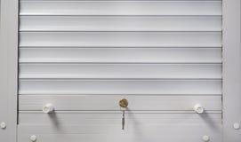 Abat-jour de blanc avec une serrure sur la fenêtre Photographie stock libre de droits