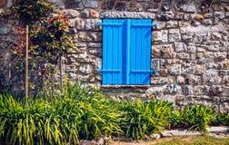 Abat-jour de fenêtre bleus fermés à la maison en pierre Image stock