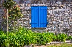 Abat-jour de fenêtre bleus fermés à la maison en pierre Images libres de droits