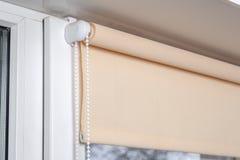 Abat-jour de rouleau beiges de panne d'électricité sur la fenêtre Photographie stock libre de droits