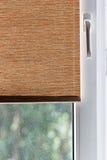 Abat-jour de tissu de Brown sur la fenêtre en plastique blanche Images libres de droits