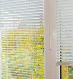 Abat-jour vénitiens blancs sur la fenêtre en plastique dans le jour d'automne Photographie stock libre de droits