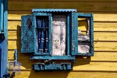 abat-jour vénitiens en bois bleus et un mur jaune Photographie stock