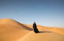 With Abaya in sandunes. A woman in abaya in sanddunes in Liwa Desert, Aby Dhabi, UAE Stock Photos