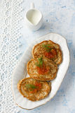 Сabbage pancakes. Vegetable pancakes with cabbage on a white plate with sour cream sauce Royalty Free Stock Image