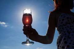 Abbagliamento del sole in un vetro di vino rosato immagine stock
