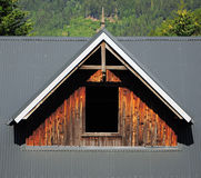 Abbaino con il pannello di legno sul tetto grigio dipinto del metallo Fotografie Stock Libere da Diritti